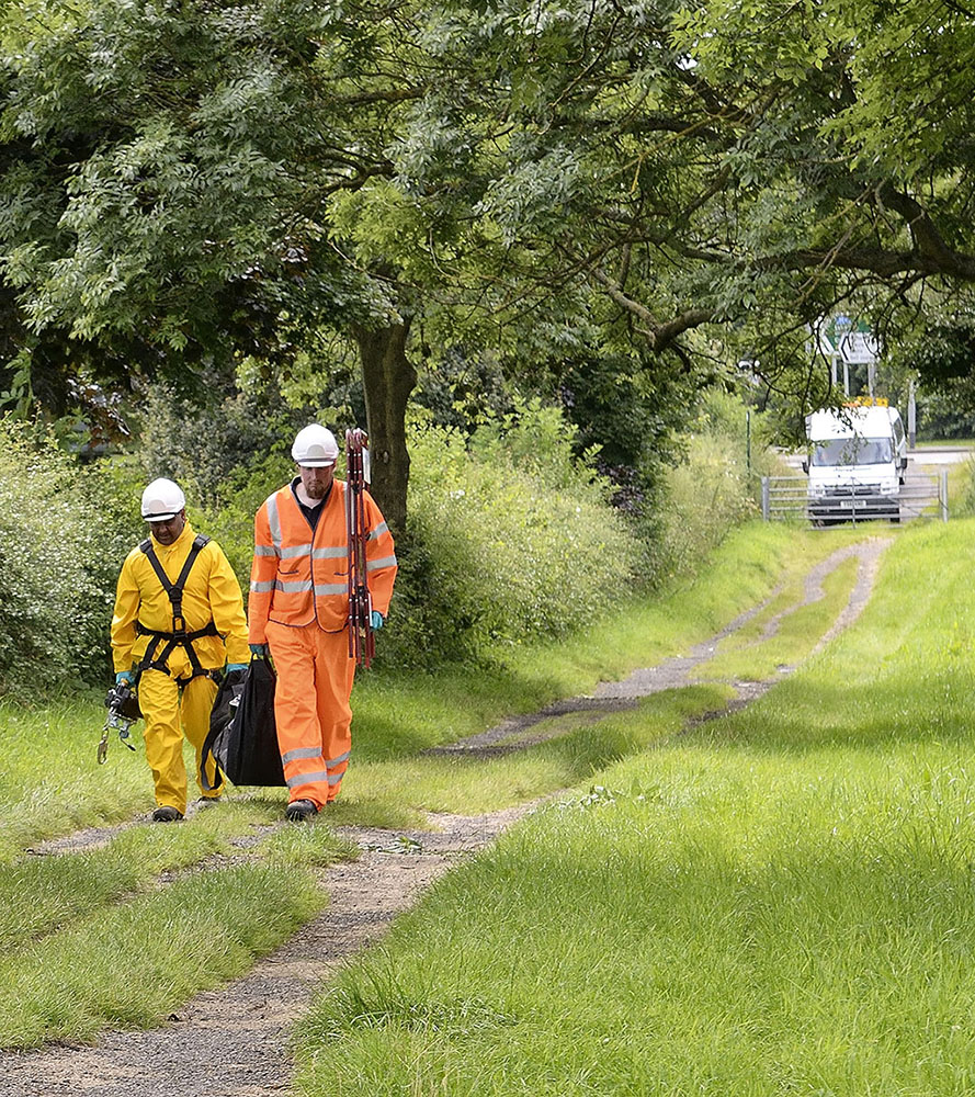 Location photography, workmen with equipment walk down a lane